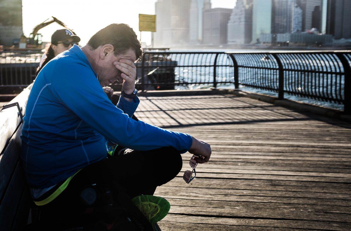 Ledsen man som sitter på en pir i träningskläder.
