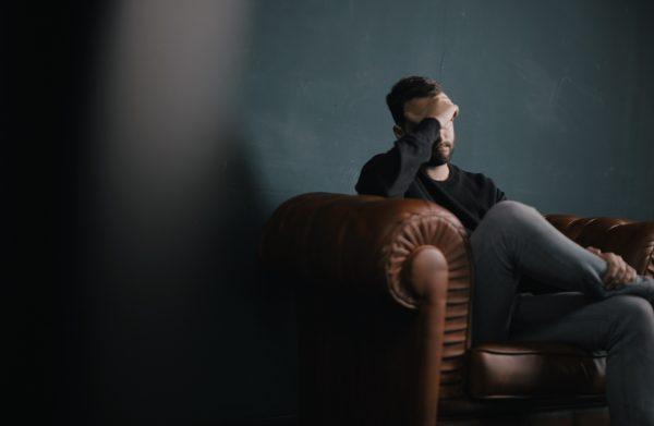 Man som sitter i en soffa och täcker sitt ansikte med handen.